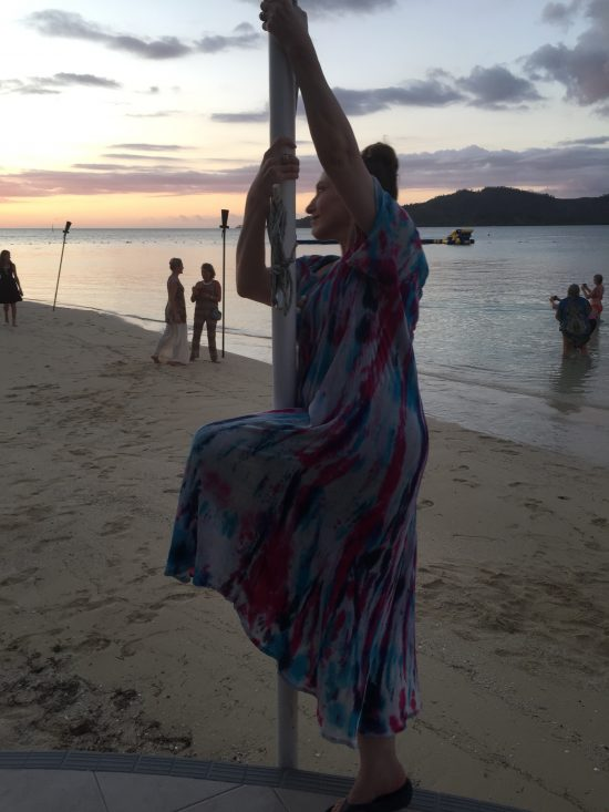 Bonnie Gillespie starts a pole trick in Fiji while others get selfies with the sunset, Feb. 2020